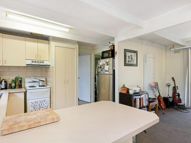 The kitchen leads to a third bedroom at the back of the home.