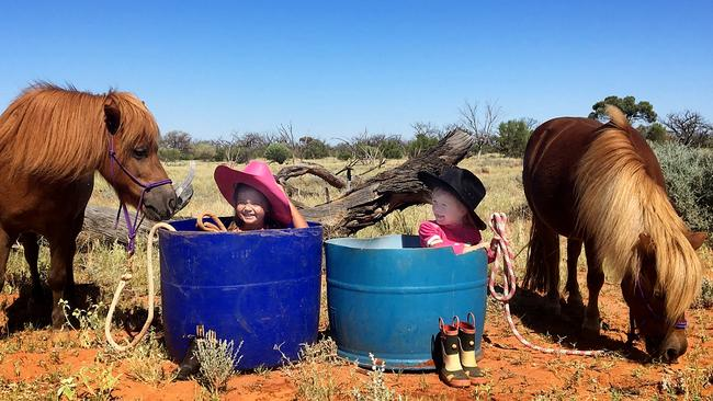 Beating the heat in Roxby Downs is Grace, 3, with pony Strady and Oivia-Lei, 2, with Poppy. Lianne Crowther