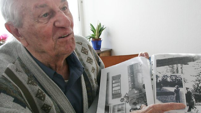 In this March 10, 2005 file photo Hitler's bodyguard Rochus Misch points to a photo of Adolf Hitler in his house in Berlin. Misch, who was the last remaining witness to the Nazi leader's final hours in his Berlin bunker, has died aged 96. Picture: AP