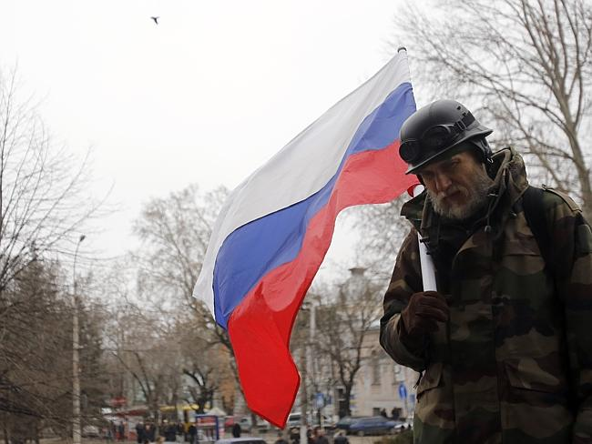 Flagging trouble ... a pro-Russian demonstrator holds a Russian flag during a protest in front of a local government building in Simferopol, Crimea, Ukraine. Picture: AP / Darko Vojinovic