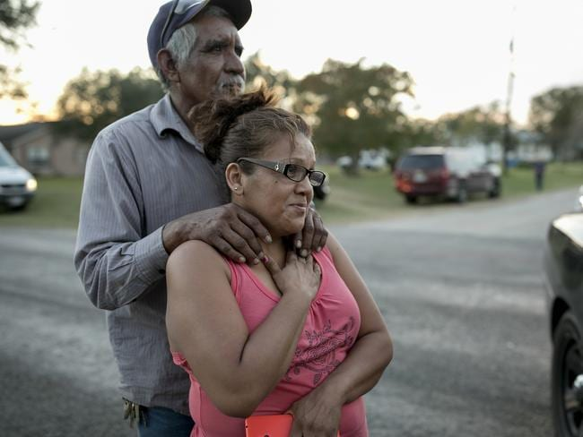 Enrique and Gabby Garcia watch investigators at the scene of a mass shooting at the First Baptist Church in Sutherland Springs, Texas. Picture: AP