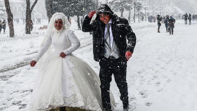 A newly married couple walk during snowfalls in Istanbul. Picture: AFP.