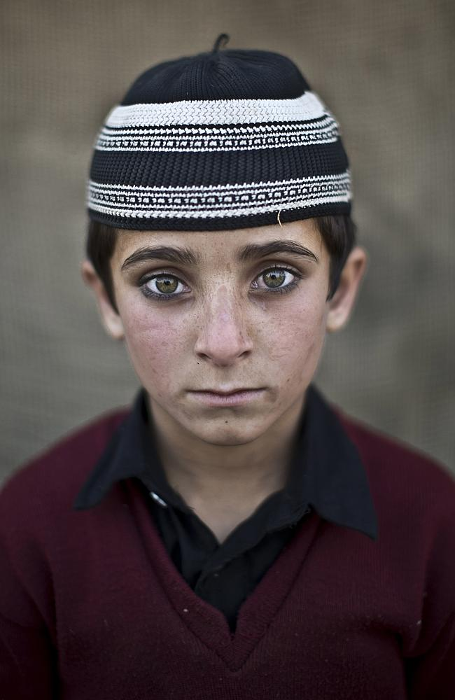 In Afghan refugee boy, Hayat Khan, 8, poses for a picture, while playing with other children in a slum on the outskirts of Is...