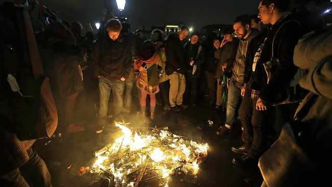 Protesters stand by a fire, after they burned a puppet depicting former British Prime Minister Margaret Thatcher, during a party to mark her death, in central London's Trafalgar square, Saturday, April 13, 2013. (AP Photo/Lefteris Pitarakis)