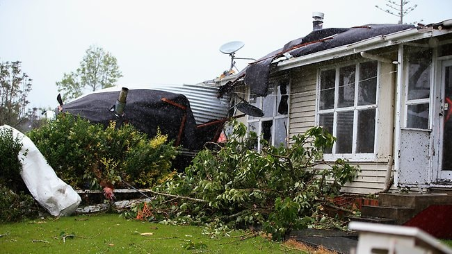 Uprooted trees and storm debri are scattered around the Auckland suburb of Hobsonville. Picture: Getty