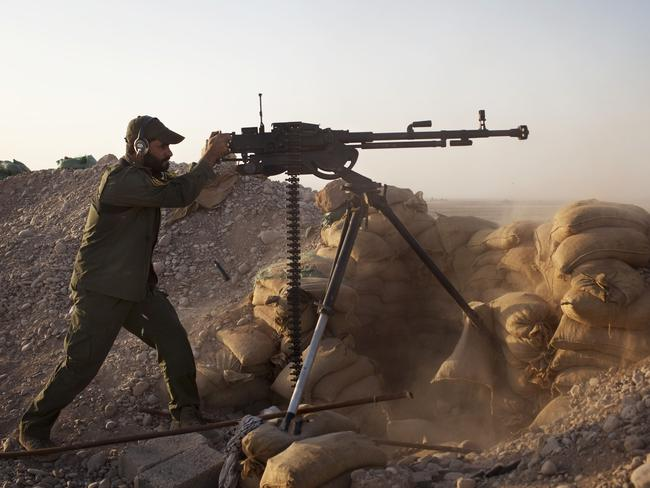 An Iraqi soldier fires a machine gun towards Islamic State. AFP PHOTO/ JM Lopez