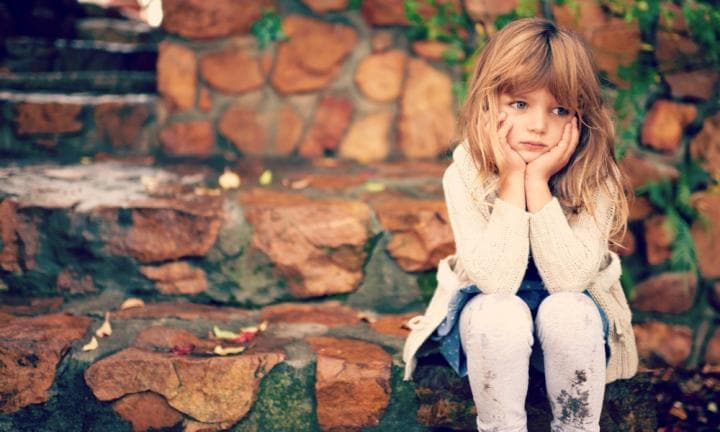 A cute little girl looking lonely while sitting outside on an autumn day