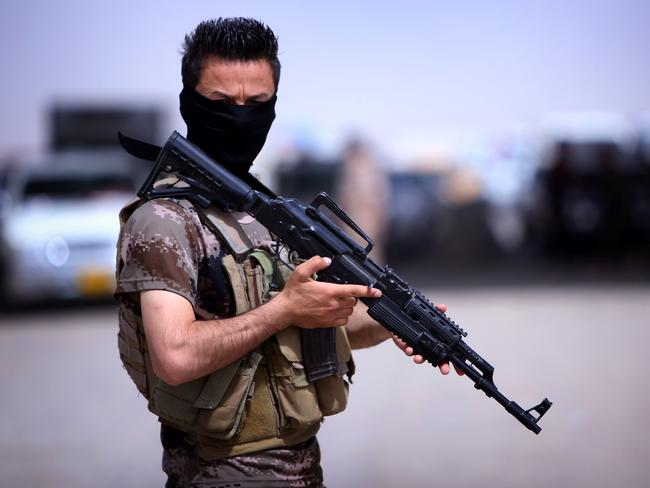 Enemies on all sides ... a masked Peshmerga fighter from Iraq's autonomous Kurdish region guards a temporary camp set up to shelter Iraqis fleeing violence in the northern Nineveh province. The minority Kurds have in the past been targeted by Iraq, Iran and Turkey.