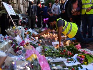 A man adds a single rose to a mound of messages and floral tributes in Albert Square in Manchester, northwest England on May 23, 2017, in solidarity with those killed and injured in the May 22 terror attack at the Ariana Grande concert at the Manchester Arena. Twenty two people have been killed and dozens injured in Britain's deadliest terror attack in over a decade after a suspected suicide bomber targeted fans leaving a concert of US singer Ariana Grande in Manchester. British police on Tuesday named the suspected attacker behind the Manchester concert bombing as Salman Abedi, but declined to give any further details. / AFP PHOTO / Ben STANSALL