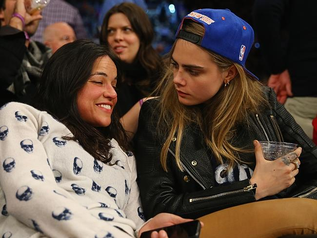 Michelle Rodriguez sits with model Cara Delevingne during the game between the New York K