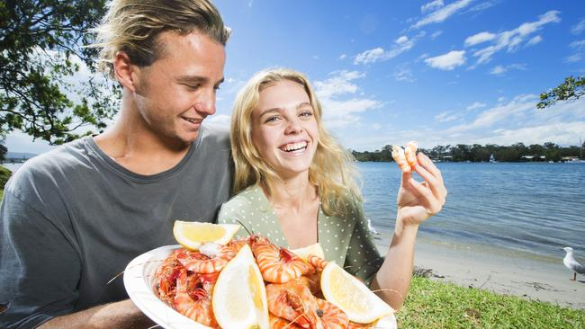 Oliver Reeves, 18, and Molly Bagnara, 18, enjoy some Mooloolaba-caught prawns by the Noosa River for lunch. Picture: Lachie Millard