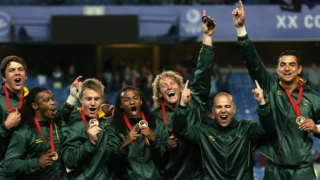 Members of the the South African sevens team celebrate on the podium after winning the gold medals.