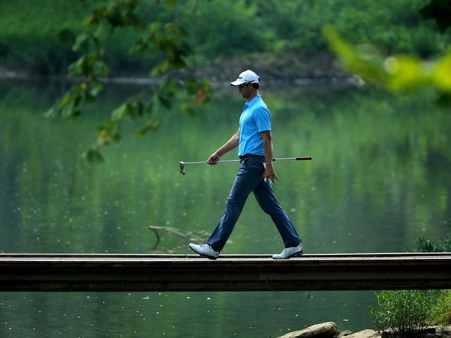 Adam Scott crosses a bridge during a practice round prior to the start of the 96th PGA Championship.