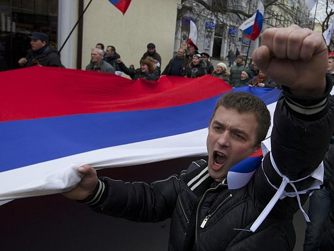 "Military force ... Locals Russian flags and shout slogans during a rally in Crimean capital Simferopol, Ukraine. Russian President Vladimir Putin was granted parliamentary permission to use the country's military in Ukraine, moving to formalise what Ukrainian officials described as an ""invasion""."