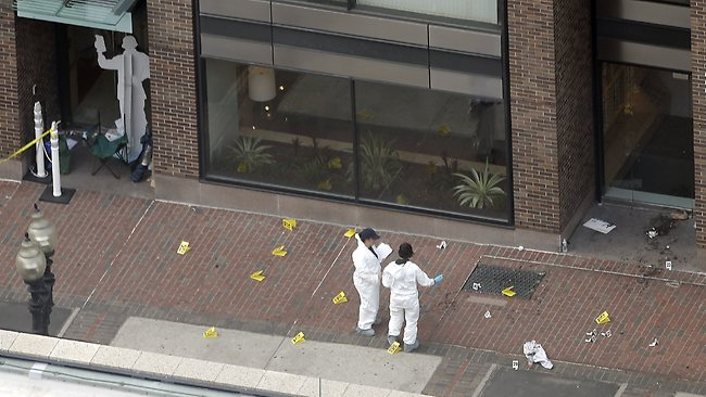 People in hazardous materials suits investigate the scene at the first bombing on Boylston Street in Boston.