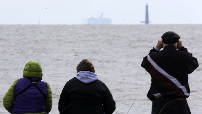 Residents sit on the shore and watch as the cruise ship Carnival Triumph is visible near Dauphin Island, Ala., Thursday, Feb. 14, 2013. The ship with over 1,000 passengers aboard has been idled for nearly a week in the Gulf of Mexico following an engine room fire. (AP Photo/Dave Martin)