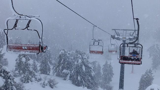 A skier rides a chair lift during a snowstorm in the Troodos Massive in the Mediterranean Island of Cyprus. Picture: AFP.
