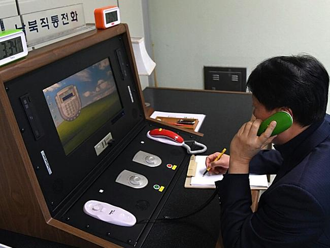 A South Korean government official communicates with a North Korean officer during a phone call on the dedicated communications hotline at the border village of Panmunjom, South Korea. Picture: Getty