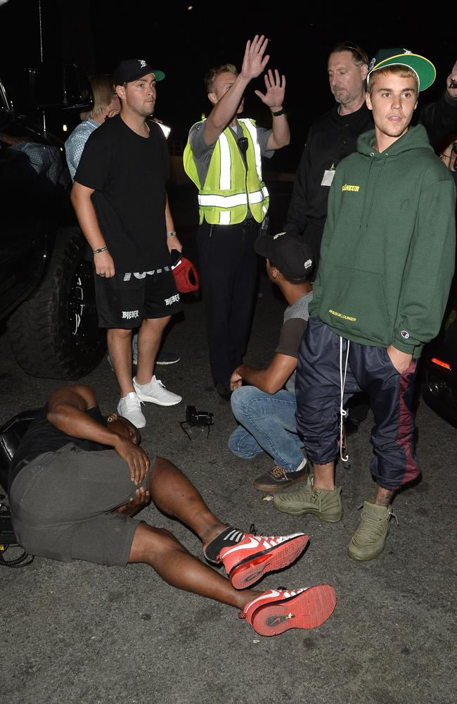 Justin Bieber with the photographer he accidentally ran over after leaving Hillsong. Picture: Splash News