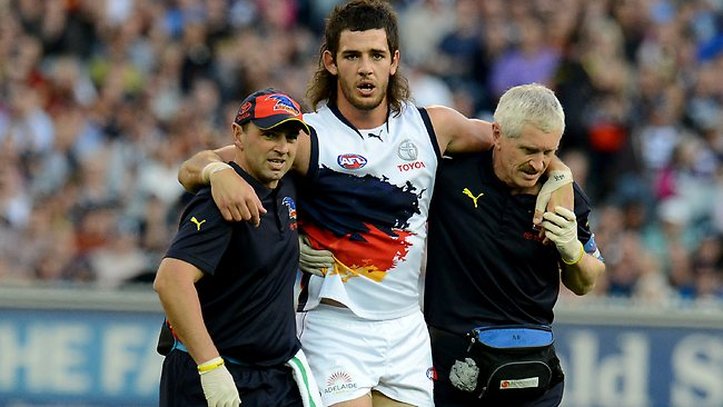 Adelaide Crows forward Taylor Walker being helped off the MCG by trainers. Picture: Wayne Ludbey.