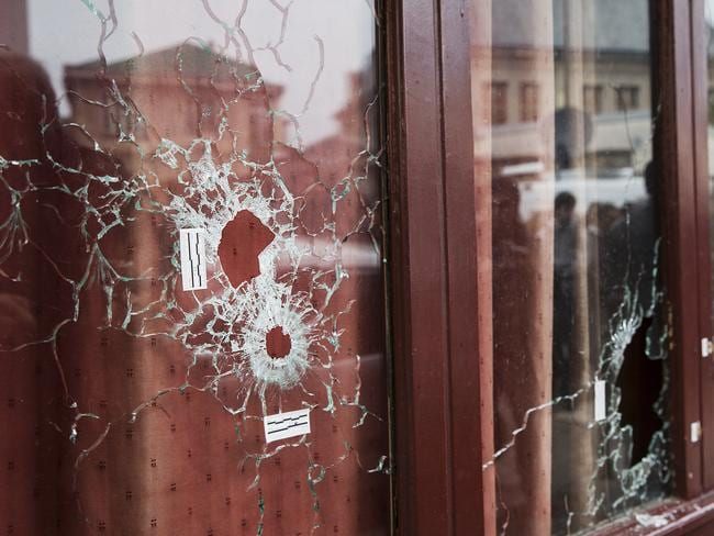 Aftermath .. bullet holes in the windows of Le Carillon Cafe. Picture: Ella Pellegrini