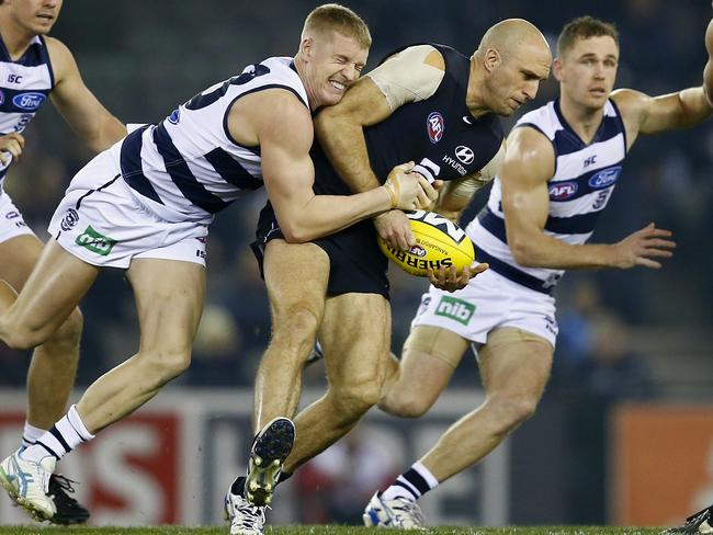 Chris Judd tackled by Josh Caddy in the middle. Pic: Michael Klein.