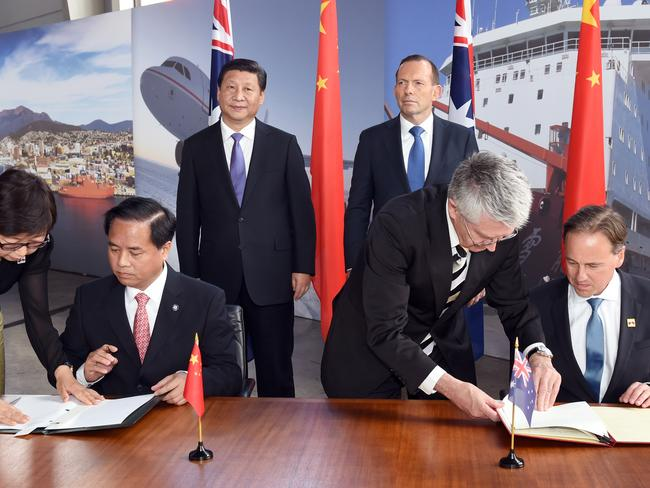 Chinese President Xi Jinping and Australian Prime Minister Tony Abbott look on as China's Administrator of the State Oceanic Administration, Liu Ciqui, and Australia's Environment Minister, Greg Hunt, sign a Memorandum of Understanding.