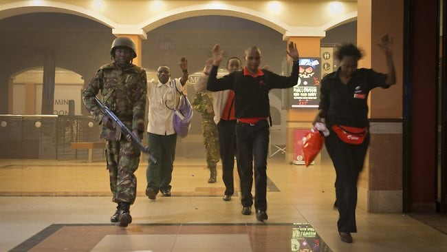 Civilians who had been hiding during the gun battle hold their hands in the air as a precautionary measure before being searched by armed police leading them to safety, inside the Westgate Mall in Nairobi, Kenya Saturday, Sept. 21, 2013. Gunmen threw grenades and opened fire Saturday, killing at least 22 people in an attack targeting non-Muslims at an upscale mall in Kenya's capital that was hosting a children's day event, a Red Cross official and witnesses said. (AP Photo/Jonathan Kalan)