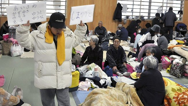 Toshihito Aisawa, 9, holds up signs with the names of his family and cousins, who have been missing since March 11 massive earthquake and tsunami, at an evacuation center in Ishinomaki, northern Japan / AP