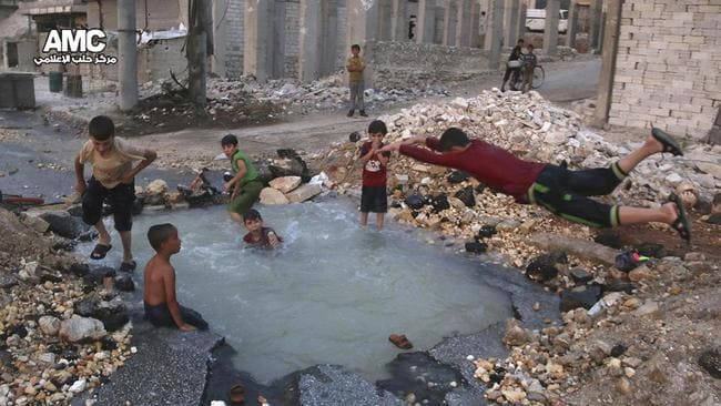 Syrian boys dive into a hole filled with water that was caused by a missile attack in the rebel-held neighbourhood of Sheikh Saeed in Aleppo province, Syria. Picture: Aleppo Media Center via AP