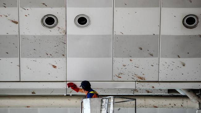 A worker cleans the blood splashed on the roof of the international departure terminal in Istanbul's international airport after three suicide bombers. Picture: Gokhan Tan/Getty Images