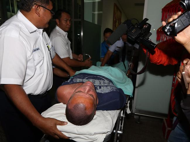 Gregory Butler was escorted out of Bali airport in an ambulance gurney. Picture: