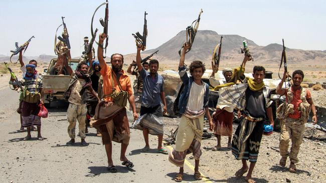Yemeni fighters loyal to the Saudi-backed Yemeni president pose for a picture raising their machine guns on April 15, 2017, on the road leading to Khaled Ibn Al-Walid base, 30 kilometres (20 miles) east of the government-held Red Sea port town of Mokha which pro-government forces retook in February. Picture: AFP / Saleh Al-Obeidi.