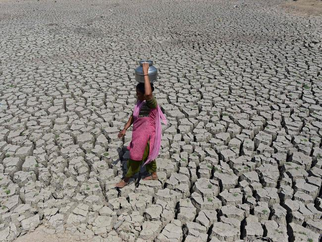An Indian woman walking on the parched bed of Chandola Lake with a metal pot on her head to fetch water in Ahmedabad. Extreme weather caused some $US129 billion in economic losses last year, said a report on October 30, 2017 that warned the tab will rise as a changing climate boosts droughts, storms and floods. Picture: Sam Panthaky