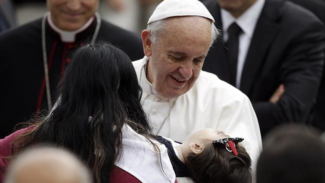 Pope Francis holds a child during the weekly general audience in St. Peter's Square, at the Vatican, on November 13. Picture: AP