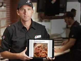 Domino's multi-unit franchisee Leroy Day holds a laptop with a Facebook comment derogatory about the pepperoni on a pizza order. Picture: Domino's