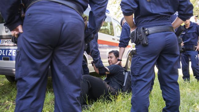 A man is detained by policemen at a checkpoint.