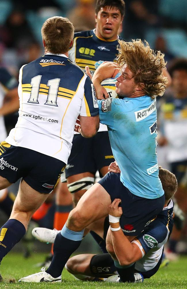Waratahs captain Michael Hooper is met by the Brumbies defence earlier this year.