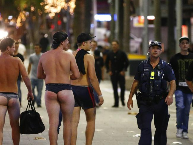 Schoolies in Surfers Paradise   For : The Courier Mail    26/11/16 Police walk past schoolies in caville ave  at Surfers Paradise Photo :  Jason O'Brien
