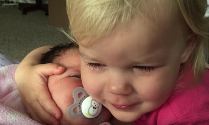 Grumpy toddler's tears are dried after a cuddle from her baby sister