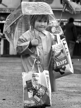 A child holds showbags in the rain at the Royal Adelaide Show in 1974.