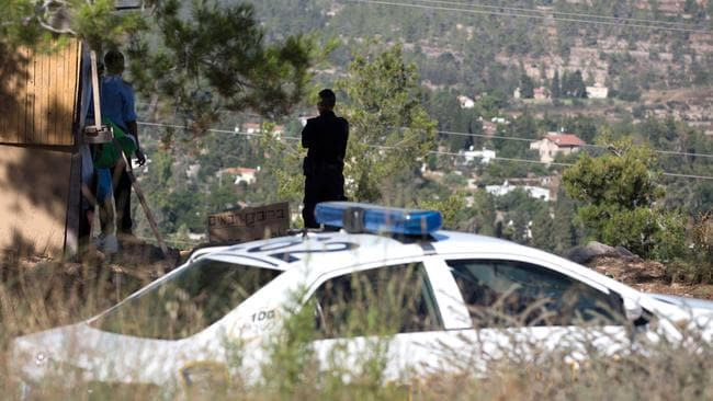 Manhunt ... Israeli police search the area after a body of a Palestinian youth was found in Jerusalem's forest. Picture: MENAHEM KAHANA