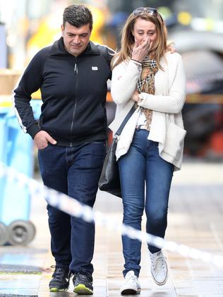 A couple, visibly upset, leave the scene in Rozelle.