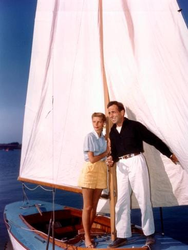 Lauren Bacall and her husband, Humphrey Bogart (1899-1957), support themselves by holding the mast on a small sailboat, circa 1950. Picture: Getty