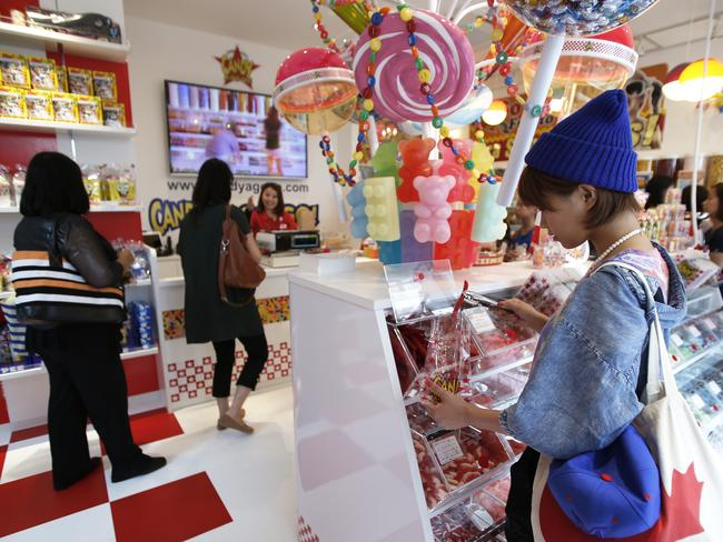 Customers shop for candies at a Candy-A-Go-Go bulk confectionery store at the Cute Cube Harajuku commercial complex in the shopping district of Harajuku.