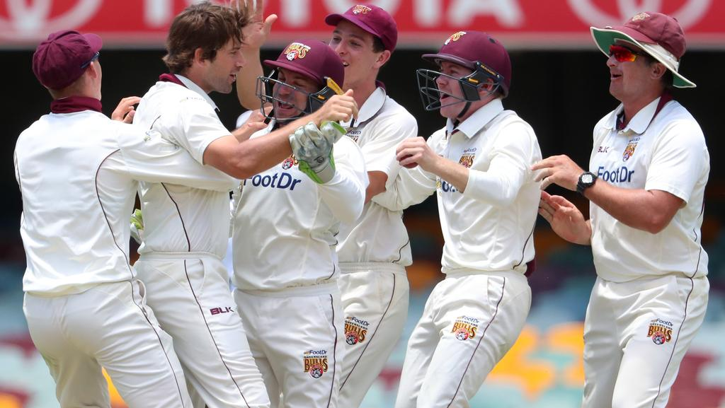 Joe Burns celebrates with team mates after getting the wicket of Jake Doran.