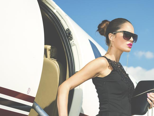 Young sensual businesswoman, or famous fashion model, leaving private jet airplane upon arrival at travel destination. She is wearing black top without sleeves, sunglasses and holding a purse.