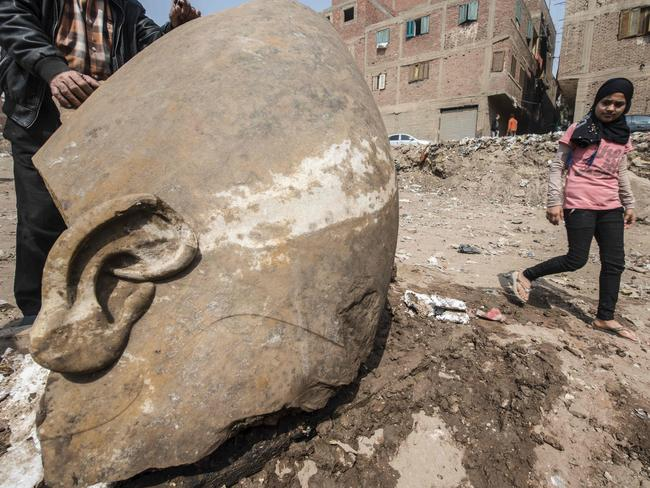An Egyptian girl walks past the head of a statue at the site of a new discovery by a team of German-Egyptian archaeologists in Cairo's Mattarya district on March 9, 2017. Picture: Khaled Desouki