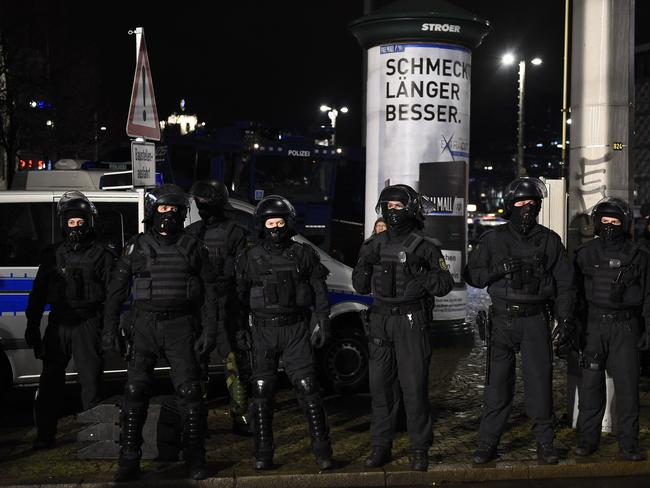 Police officers in riot gear watch protesters from the PEGIDA movement in Leipzig. Picture: AFP / Tobia Schwarz