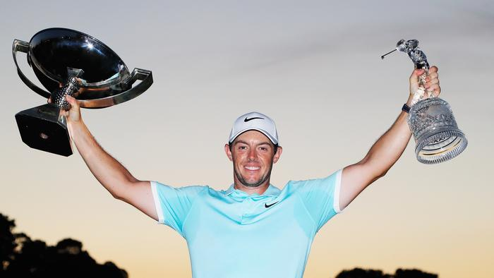 Rory McIlroy poses with the FedExCup and TOUR Championship trophies.